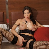 Gorgeous brunette transsexual Mariana Cordoba posing in fishnet stockings