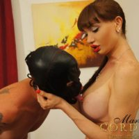 Huge-titted brown-haired trans-girl Mariana Cordoba getting blowjob from stud in leather fetish mask