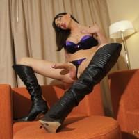 Brunette tranny Mariana Cordoba masturbating huge cock in long black boots