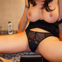 Busty TS woman Mariana Cordoba jerks off doing her housework in rubber gloves