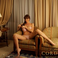 Busty trans woman Mariana Cordoba slides her panties aside to masturbate on a chair
