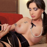 Hung shemale pornstar Mariana Cordoba strikes great solo poses in fishnets on a bed