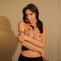 Gorgeous brunette transsexual Mariana Cordoba posing in fishnet stockings