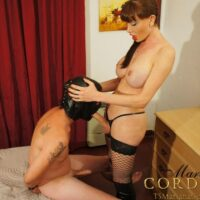 Busty black-haired ts Mariana Cordoba getting a blow job from a stud in a leather hood